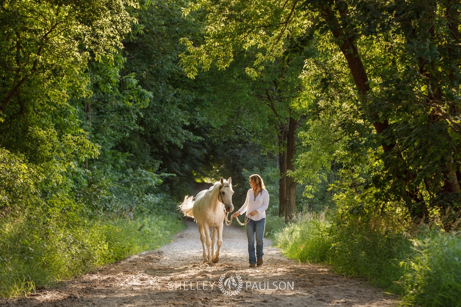 High School Senior Girl walking with Horse