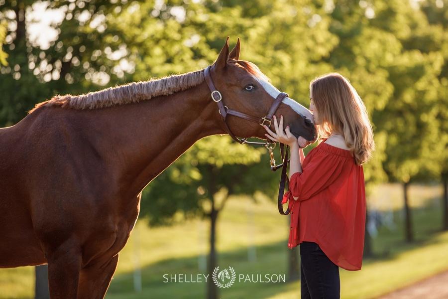 High school senior girl kissing her horse.