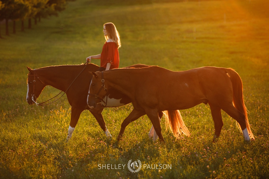 Photo of a girl riding her horse while leading another.