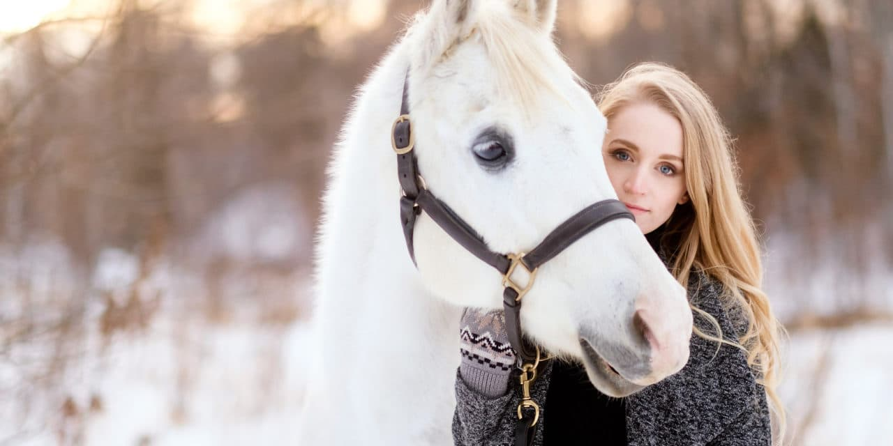 Photo of a woman and her horse in winter