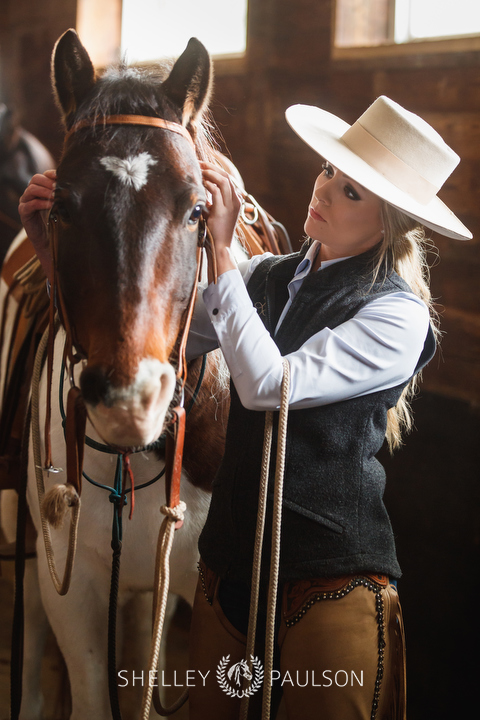 Photo of a woman bridling a horse