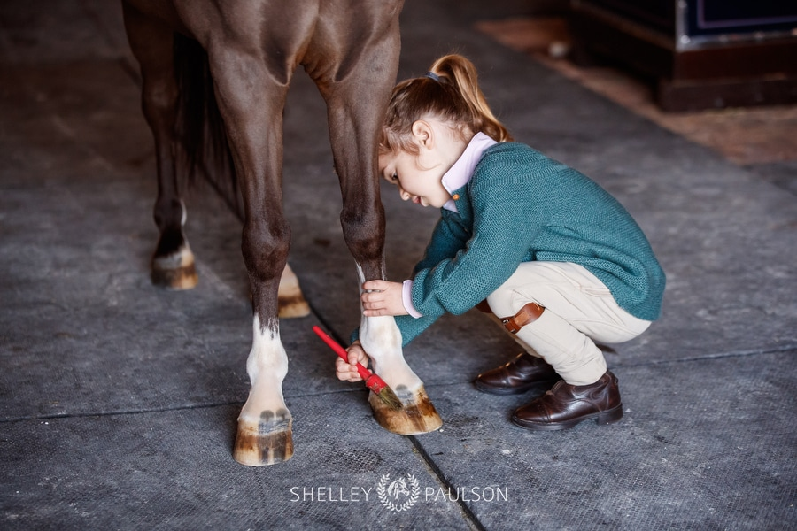 Photo of a girl polishing her pony's hooves